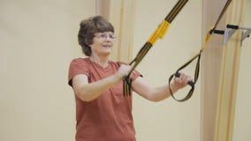 Äldre kvinna som ut sträcker och att göra sjukgymnastikövningar i konditionrum Sund gymnastik aktiva pensionärer lager videofilmer