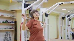 Äldre kvinna som vänder med pinnen som gör sjukgymnastikövningar i konditionrum Sund gymnastik aktiva pensionärer arkivfilmer