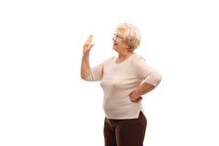 Äldre kvinna som vinkar till någon arkivbilder