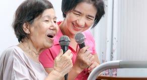 Äldre kvinnaallsång en sång med den hemmastadda dottern Royaltyfria Bilder