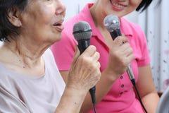 Äldre kvinnaallsång en sång med den hemmastadda dottern Arkivfoto