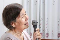 Äldre kvinnaallsång en sång på mikrofonen hemma Royaltyfri Bild