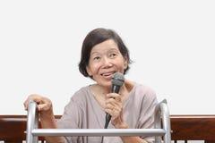 Äldre kvinnaallsång en sång på mikrofonen hemma Royaltyfri Fotografi