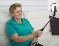 Äldre kvinnadanandesjälv-foto, selfies på hennes smarta telefon royaltyfria foton