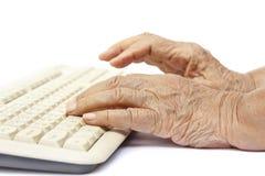 Äldre kvinnahänder på datortangentbordet Arkivfoton