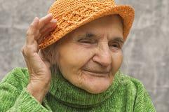 Äldre kvinnainnehavhand nästan ett öra Royaltyfria Bilder