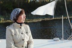 Äldre kvinnakappseglareblickar som är avlägsna på en segling, seglar Arkivbild