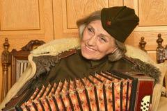 Äldre kvinnalödmetall som spelar den dragspels- closeupen arkivbilder
