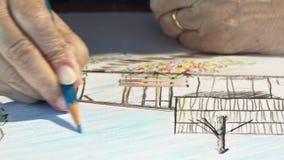 Äldre kvinnamålningfärg på hennes hobbyteckning arkivfilmer