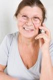 Äldre kvinnarazgovariet på en mobiltelefon Arkivfoto