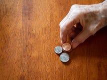 Äldre kvinnas rynkiga hand som staplar encentmynt, mynt och tiocentaren royaltyfria bilder