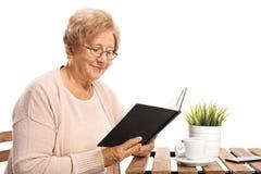 Äldre kvinnasammanträde på en kaffetabell och läsning en bok royaltyfri fotografi