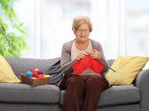 Äldre kvinnasammanträde på en soffa och ett handarbete royaltyfri bild