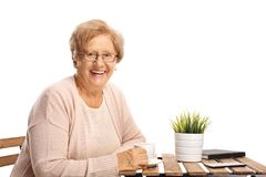Äldre kvinnasammanträde på en tabell och le för kaffe royaltyfri foto