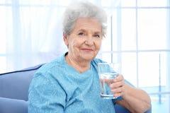 Äldre kvinnasammanträde på soffa- och innehavexponeringsglas av vatten royaltyfri fotografi