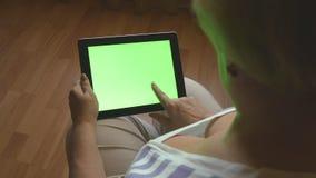 Äldre kvinnasammanträde på soffan som är hemmastadd och använder en digital minnestavlaPC med den gröna skärmen, baksidasikt Minn lager videofilmer