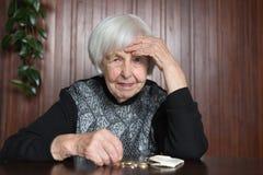 Äldre kvinnasammanträde på tabellen som räknar pengar i hennes plånbok royaltyfri foto