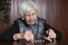 Äldre kvinnasammanträde på tabellen som räknar pengar i hennes plånbok arkivbild