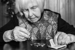 Äldre kvinnasammanträde på tabellen som räknar pengar i hennes plånbok arkivbilder