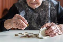 Äldre kvinnasammanträde på tabellen som räknar pengar i hennes plånbok arkivfoton