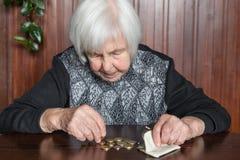 Äldre kvinnasammanträde på tabellen som räknar pengar i hennes plånbok royaltyfri bild