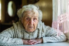 Äldre kvinnastående som sitter nära fönstret arkivbild