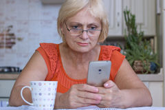 Äldre kvinnatexter på mobiltelefonen Arkivbilder