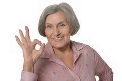 Äldre kvinnavisningtecken av oken Royaltyfria Bilder