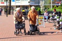 Äldre kvinnliga vänner shoppar med en rollatoreenshopping arkivfoton
