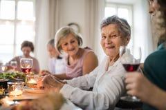Äldre kvinnor med en familj som sitter på en tabell på ett inomhus familjfödelsedagparti arkivfoto