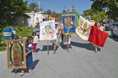 Äldre kvinnor och barn som marscherar till och med gator av Puerto Morelos som bär den mexicanska flaggan och Virgen de Guadalupe Arkivbild