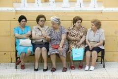 Äldre kvinnor sitter på bänk i by av sydliga Spanien av huvudvägen A49 som är västra av Sevilla Arkivbild