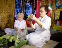 Äldre kvinnor som gör lotusblommablomman i templet, Lampang, Thailand Arkivbilder