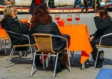 Äldre kvinnor som terrasserar med aperol, spritz coctailen i hållande ögonen på folk för gatakafét som förbi går royaltyfri fotografi