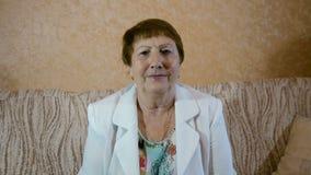 Äldre le för kvinna som ser in i kameran lager videofilmer