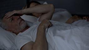 Äldre ligga för man som är sömnlöst i sänglidandehuvudvärken, gnidande huvud, problem arkivbild