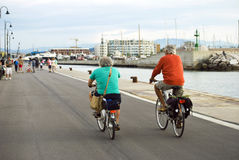 Äldre män som rider cyklar längs promenaden av Rimini, Italien Fotografering för Bildbyråer