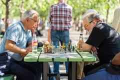 Äldre män som spelar schack i en stadsfyrkant arkivfoto