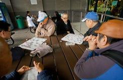 Äldre män spelar den strategiska leken för forntida kines av Go under ferier Arkivbilder