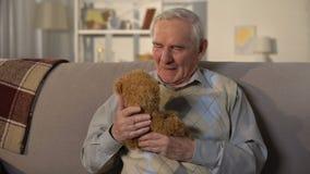 Äldre människor som kramar teddybjörn, saknade barnbarn, familjestöd stock video