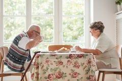 Äldre make och fru som har ett te och en kaka tillsammans på tabellen royaltyfri fotografi