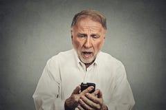 Äldre man, chockat förvånat vid vad han ser på hans mobiltelefon Royaltyfri Foto