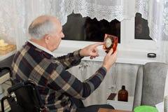 Äldre man i en rullstol som kontrollerar klockan Fotografering för Bildbyråer