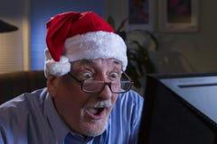 Äldre man i jultomtenhatten som ser chockad, horisontal arkivbilder