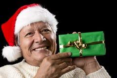 Äldre man med den Santa Cap And Green Wrapped gåvan Arkivfoton