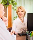 Äldre man med doktorn i klinik Arkivbild