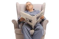 Äldre man med en tidning som sover i en fåtölj arkivfoton