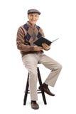 Äldre man med ett boksammanträde på en stol Arkivbilder
