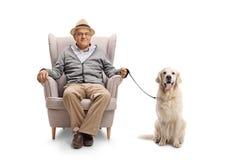 Äldre man med ett labrador retriever hundsammanträde i en fåtölj arkivbild