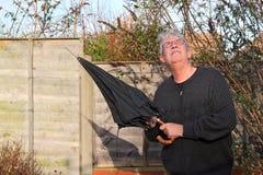 Äldre man med ett paraply som ser upp på himlen. Fotografering för Bildbyråer